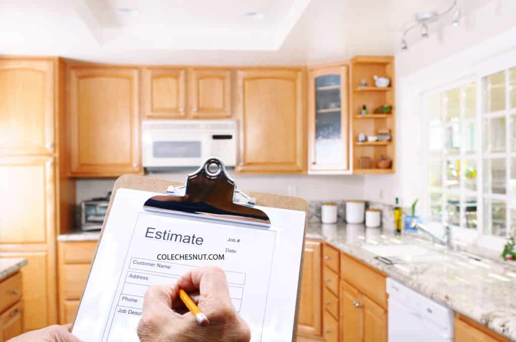 Contractor writing an estimate in a kitchen.